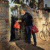 在伊拉克,一名为开发署支持的团体工作的志愿者向位于伊拉克卡尔巴拉郊区的塔里杰区的一个弱势家庭运送食品。