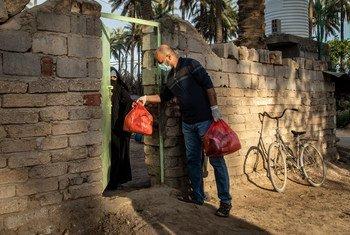 No Iraque, um voluntário que trabalha para um grupo apoiado pelo Pnud entrega uma sacola de alimentos a uma família vulnerável no distrito de Tawrij, localizada nos arredores de Karbala, Iraque.