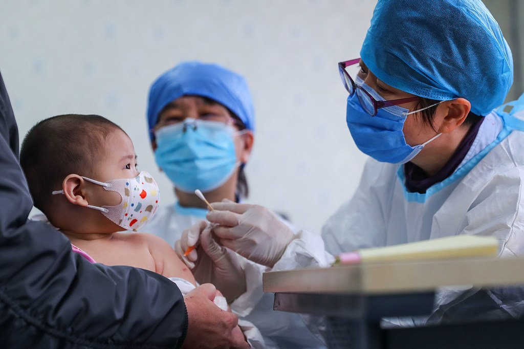 رضيع يبلغ من العمر 6 شهور يحصل على تطعيم متأخر في أحد المراكز الصحية في بيجين بالصين.