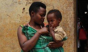 Une mère tient son enfant devant sa maison dans le camp de réfugiés de Kiziba au Rwanda.