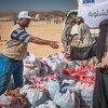 امرأة نازحة تتلقى حزمة مساعدات في موقع التوزيع في مأرب، اليمن.