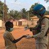 جندي حفظ سلام من بعثة الأمم المتحدة المتكاملة متعددة الأبعاد لتحقيق الاستقرار في جمهورية إفريقيا الوسطى (مينوسكا) يصب معقم اليدين في يد الطفل.