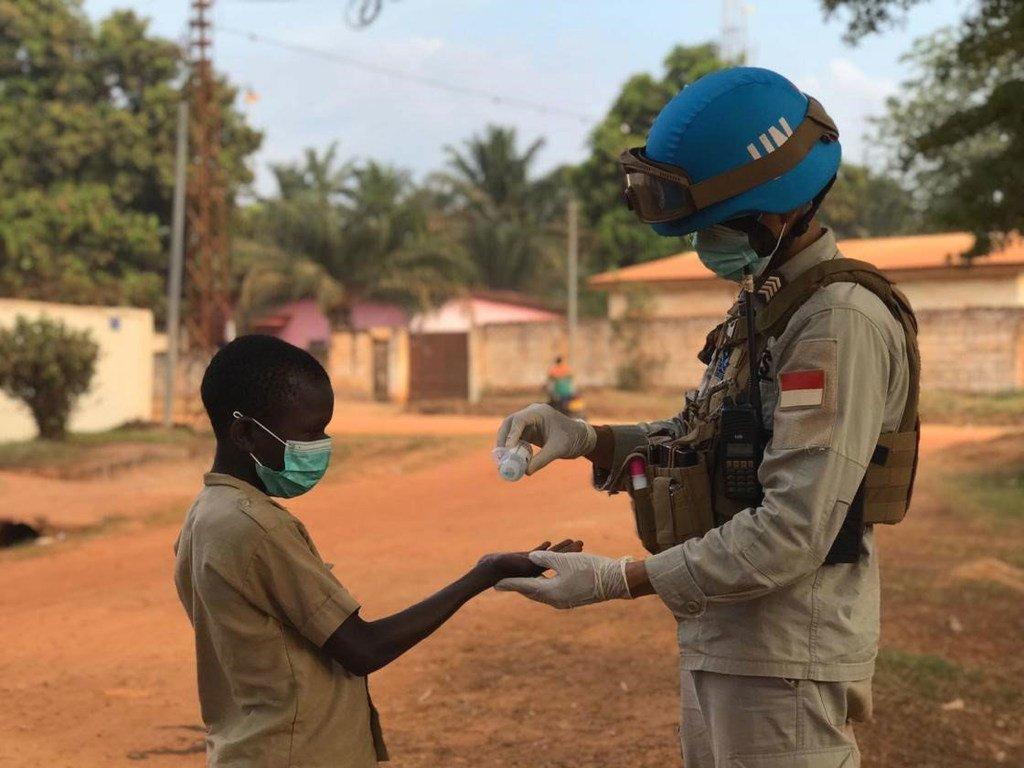 En République centrafricaine, un Casque bleu de la MINUSCA verse du gel hydroalcoolique dans la main d'un enfant.