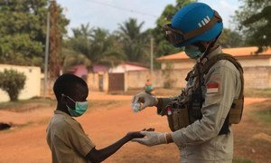 联合国中非共和国多层面综合稳定特派团的一名维和人员将洗手液倒入一名儿童的手中。