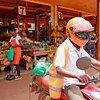 Un conducteur de SafeBoda et un vendeur de marché utilise l'application SafeBoda pour livrer de la nourriture pendant le confinement dû à la Covid-19 à Kampala, en Ouganda.