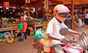 A SafeBoda rider and market vendor use the SafeBoda app to deliver food and supplies during the COVID-19 lockdown in Kampala, Uganda.