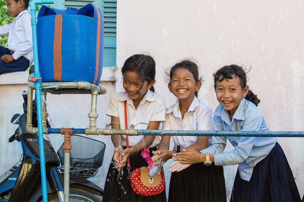 Wasichana wa shule huko Cambodia wakiosha mikono yao kwa kutumia maji kutoka kwa kituo cha shule cha WASH.
