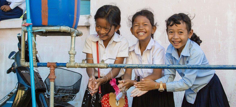 Meninas de uma escola no Camboja lavam as mãos usando a água de uma instalação da escola.