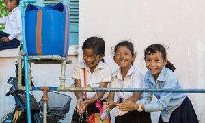 طفلات صغيرات في كمبوديا يغسلن أيديهن بالماء في مرفق للغسيل في المدرسة.