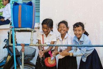 कम्बोडिया के एक स्कूल में लड़कियाँ अपने हाथों को धो रही हैं.
