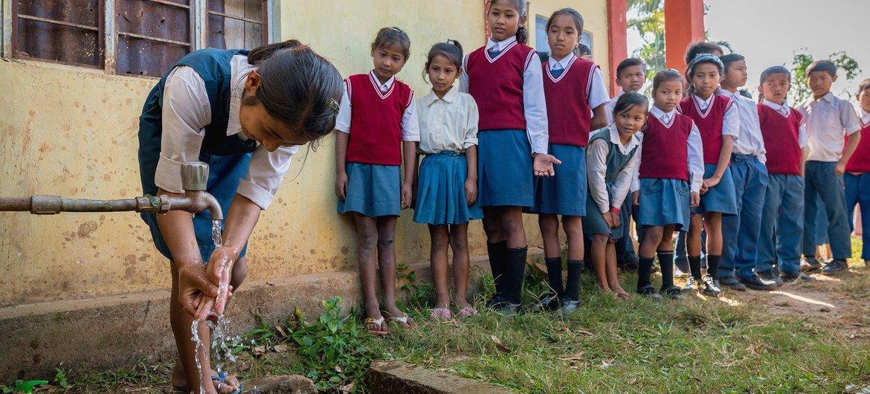 Alunos esperam na fila para lavar as mãos em uma escola em Meghalaya, na Índia.