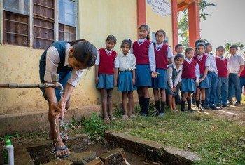 Estudiantes de una escuela en Meghalaya, India, hacen fila para lavarse las manos.