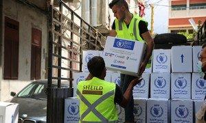 عمال يفرغون حمولة المعونات الغذائية التي أرسلها برنامج الأغذية العالمي في مركز كاراجوسيان في بيروت ، لبنان