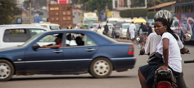 A Boda Boda rider and passenger wait at a junction in Kampala, Uganda.