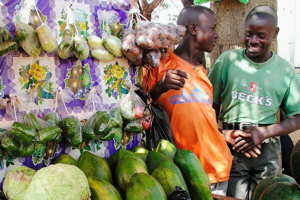 Des marchands ambulants discutent devant leur étal de fruits et legumes sur un marché de Kampala, en Ouganda