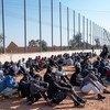 लीबिया में एक हिरासत केन्द्र में बैठे हुए प्रवासी जन. (फ़ाइल फ़ोटो)