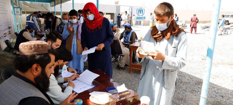 Unas personas desplazadas reciben asistencia en un centro de distribución de Kabul, en Afganistán.