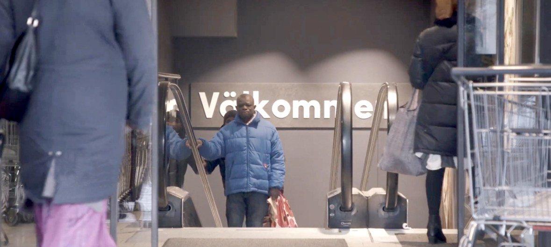 """新近抵达瑞典的移民朱利斯搭乘电梯离开一家超市,他身后的墙壁上有瑞典语写的""""欢迎""""一词。"""