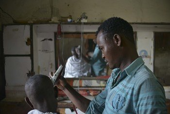 Kinyozi akimnyoa nywele mteja kwenye mji wa Belet Weyne nchini Somalia.