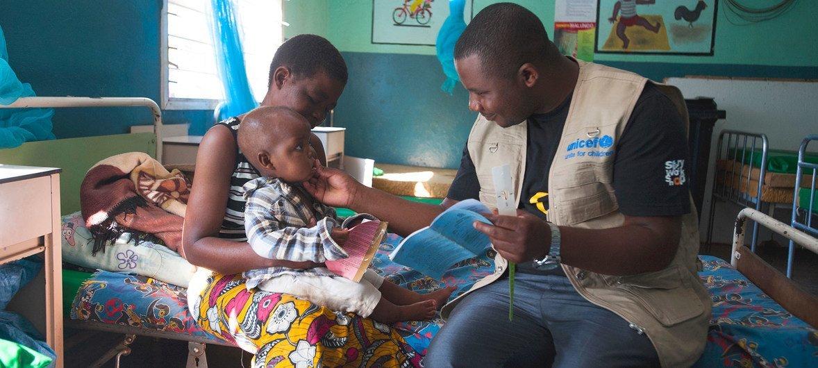 Una madre sostiene a su hijo de 18 meses mientras lo atienden en un hospital del distrito de Balaka en Malawi.