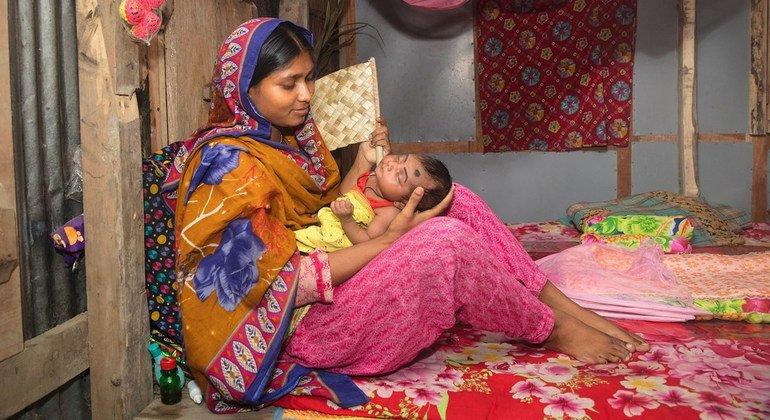 En Bangladesh, una madre sujeta a su bebé de 27 días que acaba de regresar de una hospitalización por neumonía