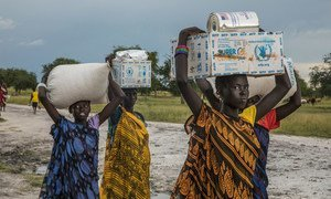 Women carry food assistance received at a WFP emergency distribution point in Thaker, Unity state, South Sudan.