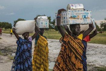 Mulheres carregam ajuda humanitária do PMA em Thaker, no Sudão do Sul