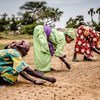 Women plant seeds while taking part in a Sahelian plant and reforestation project in Niger.