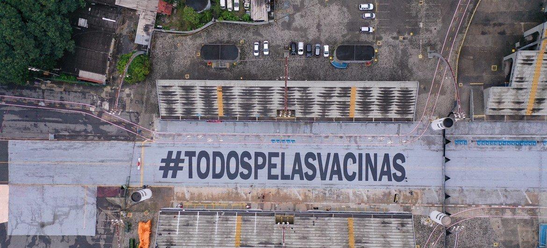 Pintura da mensagem #TodosPelasVacinas na passarela do Anhembi
