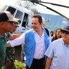 联合国哥伦比亚核查团团长卡洛斯·鲁伊斯·马谢乌(中)在前往哥伦比亚安蒂奥基亚执行实地任务时向一名前战斗人员致意。