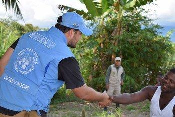 Un integrante de la Misión de Verificación de las Naciones Unidas en Colombia saluda a un excombatiente durante un viaje al departamento de Antioquia.