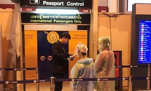 Passengers wearing face masks and disposable ponchos get their passports checked at Don Mueang International Airport in Bangkok, Thailand.