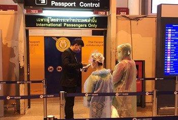Passageiros com máscaras e ponchos descartáveis no Aeroporto Internacional Don Mueang, em Bangcoc, Tailândia.