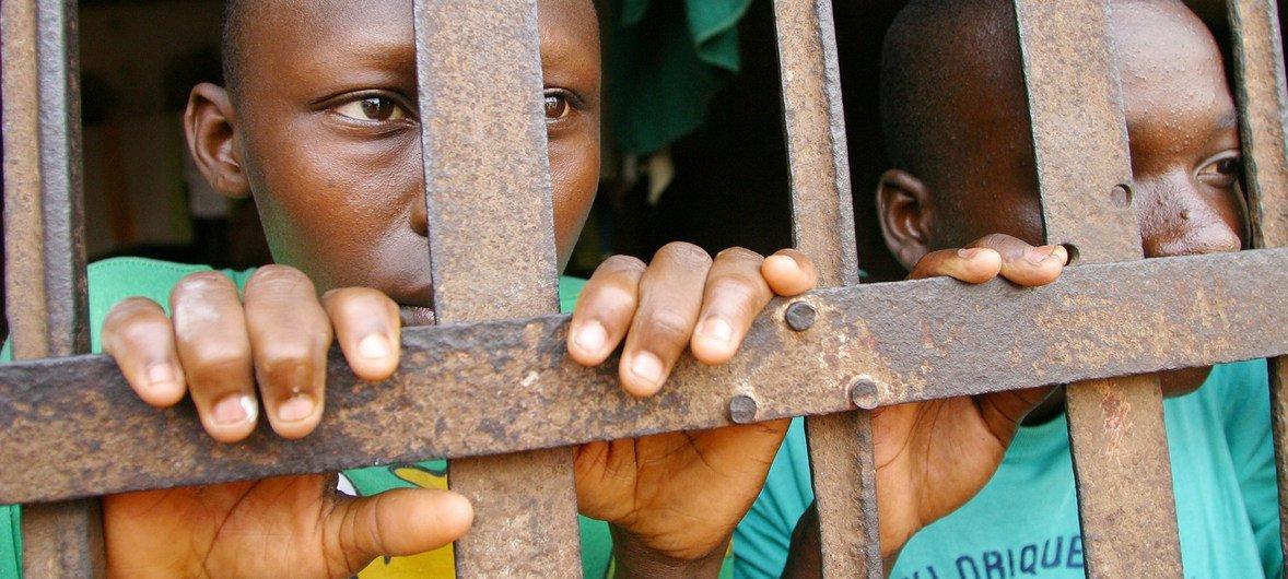 Dos jóvenes presos tras las rejas en una cárcel de Abomey, en la República de Benin.
