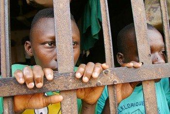 Deux jeunes prisonniers derrière les barreaux d'une prison à Abomey, au Bénin.