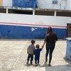 一名来自萨尔瓦多的母亲带着两个孩子走进墨西哥南部一家由难民署运营的登记中心。