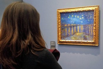 Woman at Musée d'Orsay in Paris gazes at  Vincent Van Gogh painting from 1888.