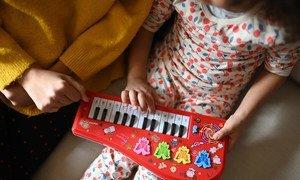 Una madre y su hija tocan un teclado mientras están en confinadas en casa durante la pandemia COVID-19.