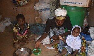 Une famille à Kaya, dans la province de Sanmatenga, au Burkina Faso, partage un repa après avoir reçu des rations du PAM.