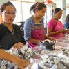 Women work in an assembly line to package handicrafts for export.