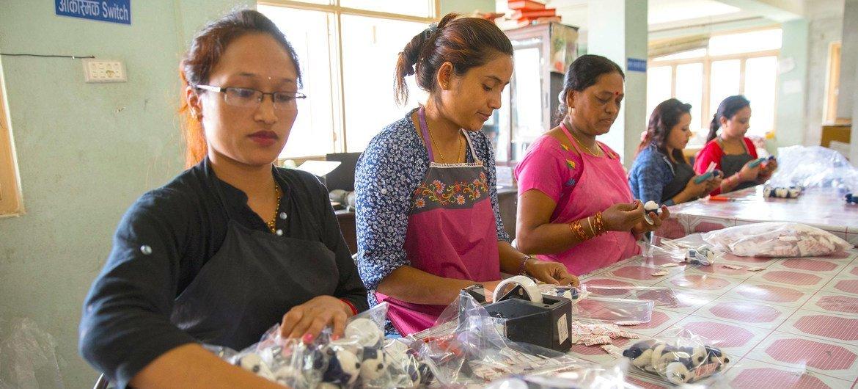 نساء يعملن في مصنع للحرف اليدوية وتغليف السلع بهدف التصدير
