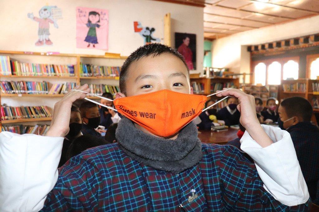 Un estudiante de sexto grado de la Escuela Secundaria Inferior Drukgyel en Paro, en Bután, muestra el mensaje en su máscara: Los héroes usan máscara.