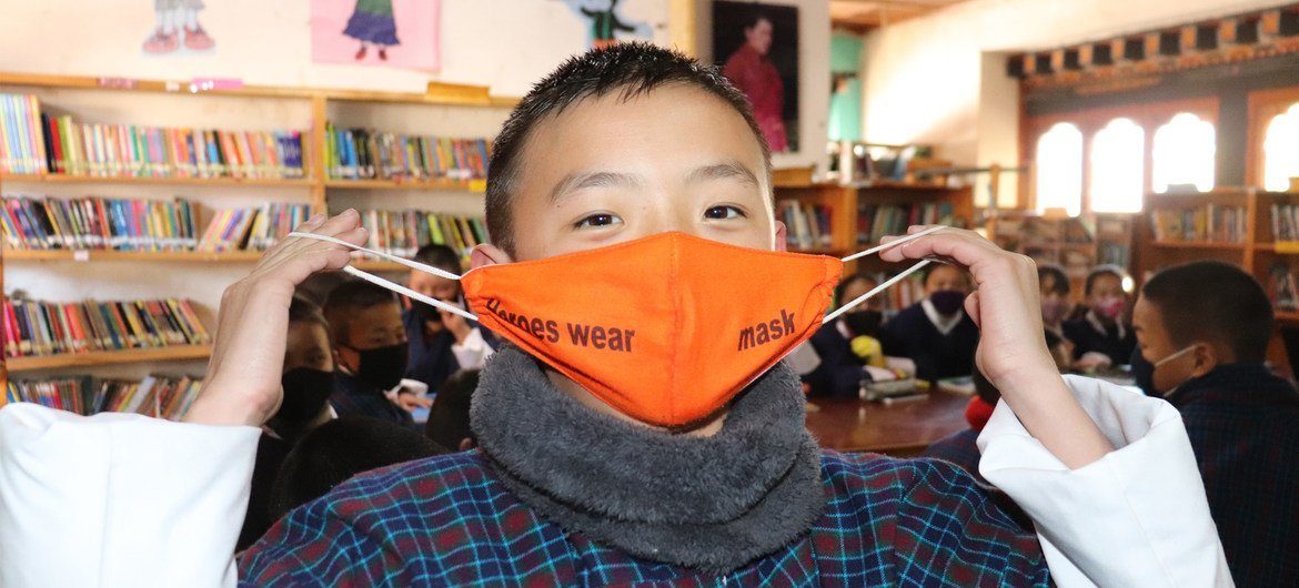 A grade six student of Drugyel Lower Secondary School in Paro, Bhutan, shows the message on his mask: Heroes wear mask.