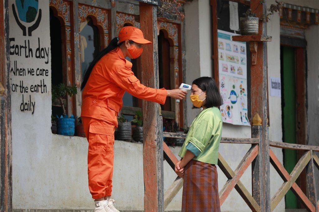 Un voluntario civil verifica la temperatura de un residente antes de que ingrese a la sala de vacunación en Tseza gewog en Dagana.