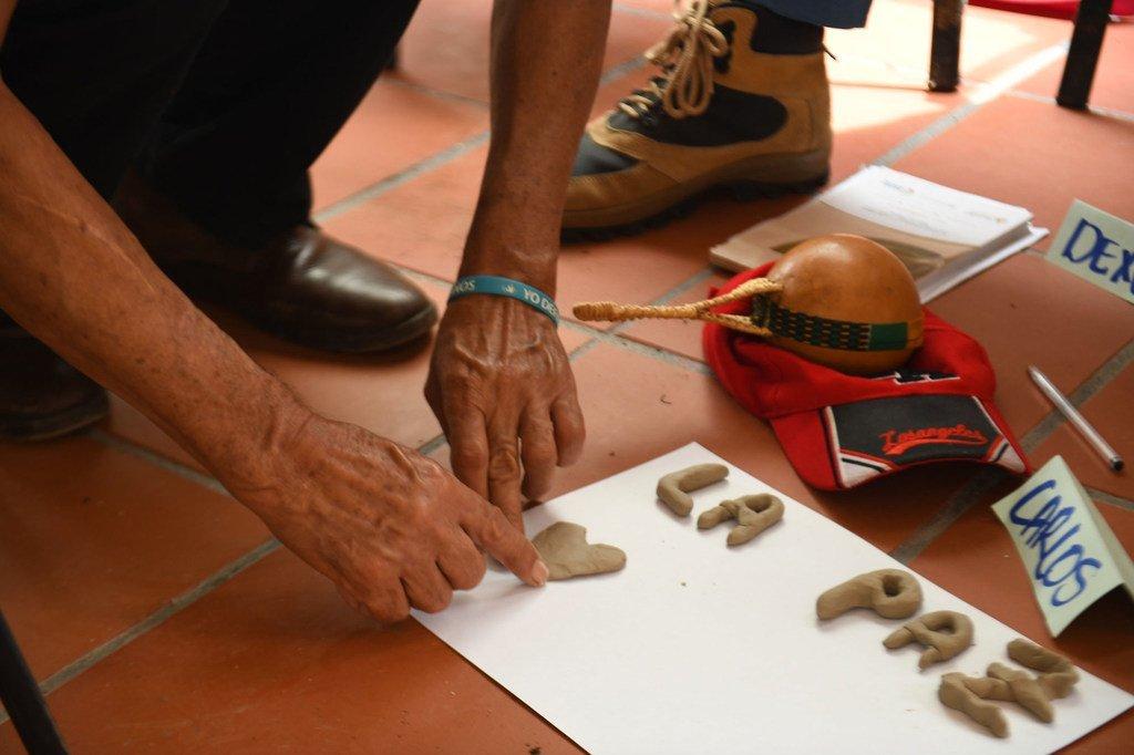 """Une personne participant à un programme de réconciliation en Colombie écrit le mot """"paix"""" en espagnol."""