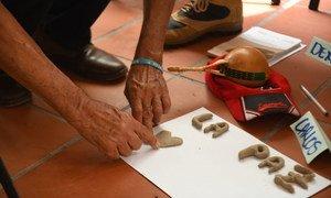 Participante en un programa de reconciliación de Colombia escribe la palabra paz.