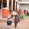 Une jeune fille au Ghana se lave les mains avant de retourner en classe.