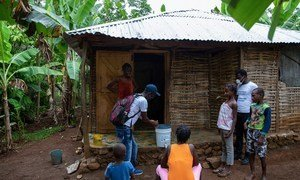 在这张地震前拍摄的照片中,儿童基金会的宣传小组访问了位于海地大湾省得一个家庭,向他们提供新冠预防技能。
