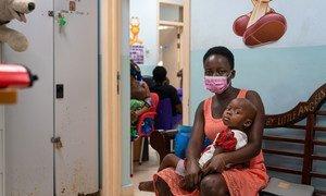 Uma menina de dois anos e sua mãe esperam para ver um médico em Accra, Gana