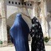两名阿富汗妇女在赫拉特省西部的一座古老清真寺附近散步。